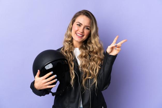 Jonge braziliaanse vrouw die een motorhelm houdt die op purpere achtergrond wordt geïsoleerd die en overwinningsteken glimlacht toont