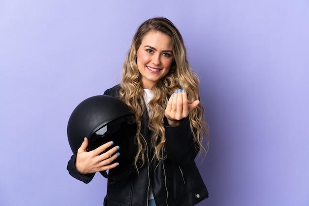 Jonge braziliaanse vrouw die een motorhelm houdt die op purpere achtergrond wordt geïsoleerd die uitnodigt om met de hand te komen. blij dat je gekomen bent