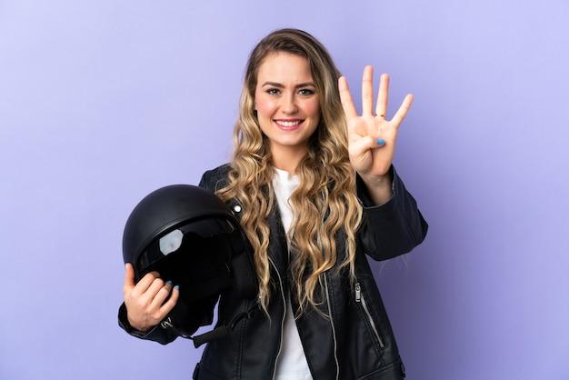 Jonge braziliaanse vrouw die een motorhelm houdt die op purpere muur gelukkig wordt geïsoleerd en vier met vingers telt