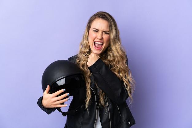 Jonge braziliaanse vrouw die een motorhelm houdt die op purpere muur wordt geïsoleerd die een overwinning viert