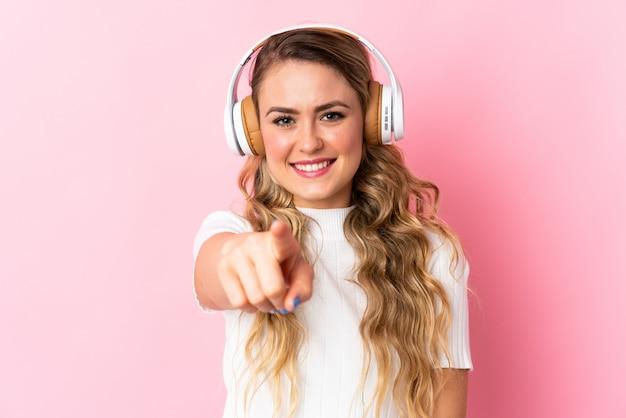 Jonge braziliaanse vrouw die op roze het luisteren muziek wordt geïsoleerd en aan de voorzijde richt
