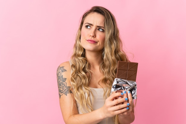 Jonge braziliaanse vrouw die op roze wordt geïsoleerd dat een chocoladetablet neemt en twijfels heeft