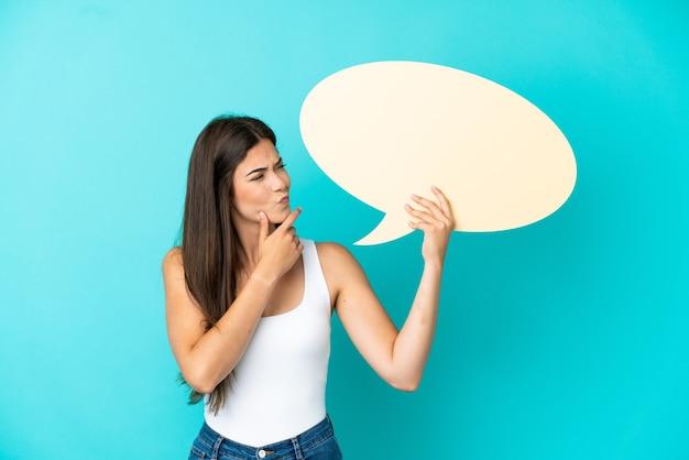 Jonge braziliaanse vrouw geïsoleerd op blauwe achtergrond met een lege tekstballon en denken