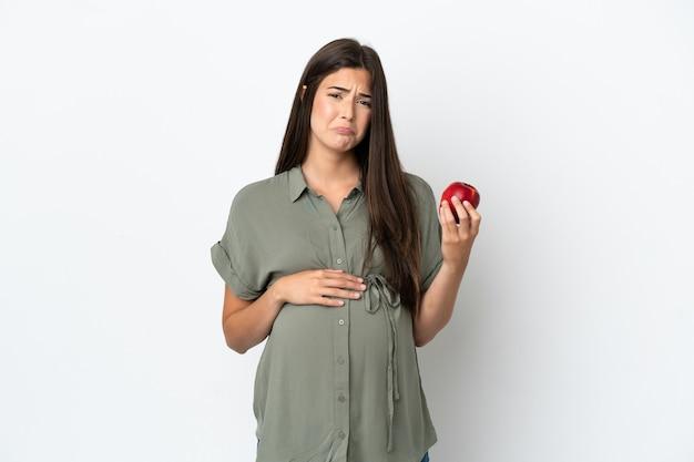 Jonge braziliaanse vrouw geïsoleerd op een witte achtergrond zwanger en gefrustreerd terwijl ze een appel vasthoudt