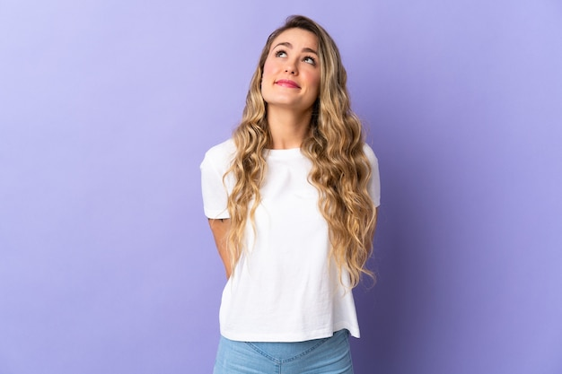 Jonge braziliaanse vrouw geïsoleerd op paars en opzoeken