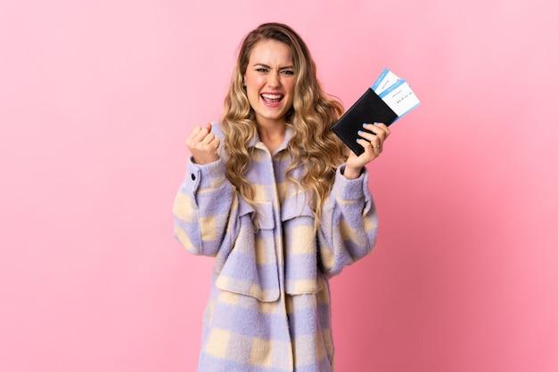 Jonge braziliaanse vrouw geïsoleerd op roze gelukkig in vakantie met paspoort en vliegtickets