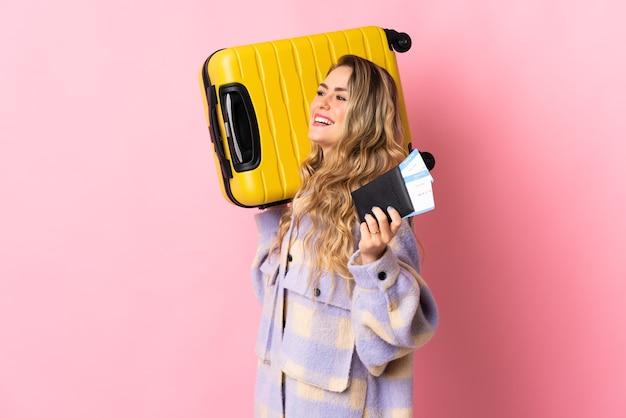 Jonge braziliaanse vrouw geïsoleerd op roze in vakantie met koffer en paspoort