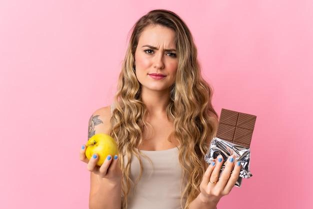 Jonge braziliaanse vrouw geïsoleerd op roze met een chocoladetablet in de ene hand en een appel in de andere