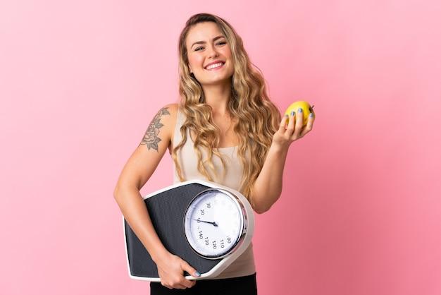 Jonge braziliaanse vrouw geïsoleerd op roze met weegmachine en met een appel