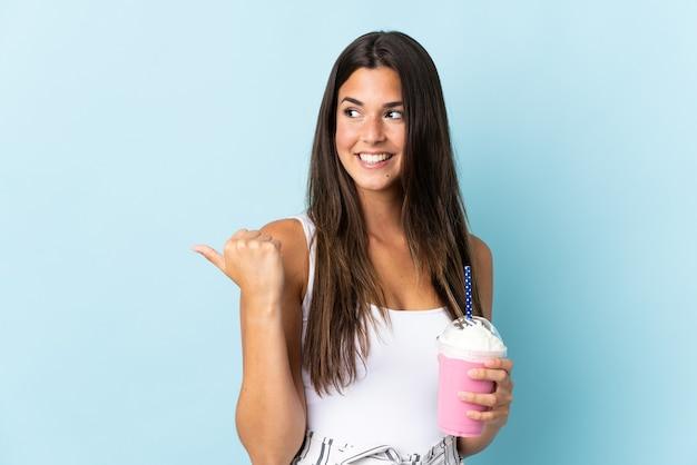 Jonge braziliaanse vrouw met aardbeimilkshake die op blauw wordt geïsoleerd dat naar de kant wijst om een product te presenteren