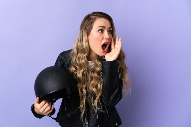 Jonge braziliaanse vrouw met een motorhelm geïsoleerd op paars schreeuwen met mond wijd open aan de zijkant