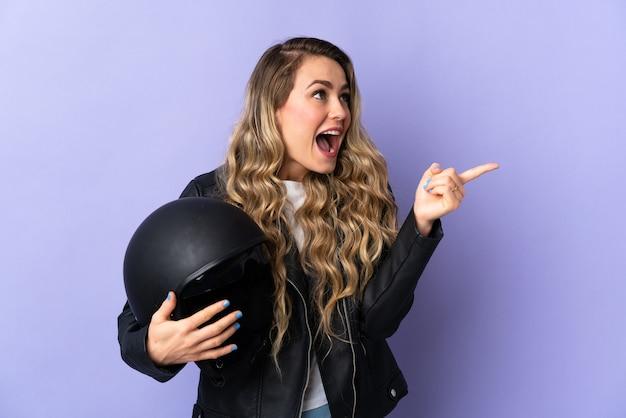 Jonge braziliaanse vrouw met een motorhelm geïsoleerd op paarse achtergrond met de bedoeling om de oplossing te realiseren terwijl ze een vinger opheft