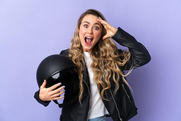 Jonge braziliaanse vrouw met een motorhelm geïsoleerd op paarse muur met verrassing expressie