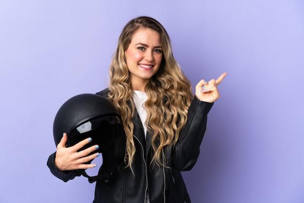 Jonge braziliaanse vrouw met een motorhelm geïsoleerd op paarse muur wijzende vinger naar de zijkant
