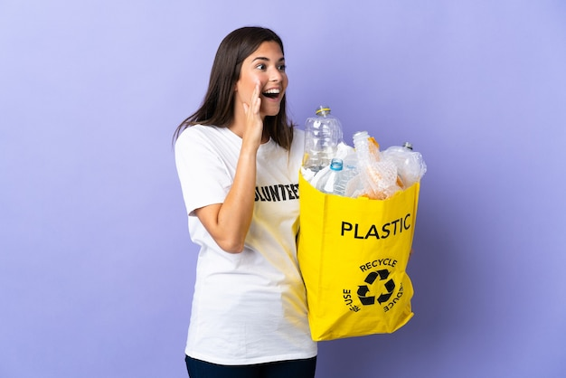 Jonge braziliaanse vrouw met een zak vol plastic flessen om te recyclen geïsoleerd op paars schreeuwen met mond wijd open aan de zijkant