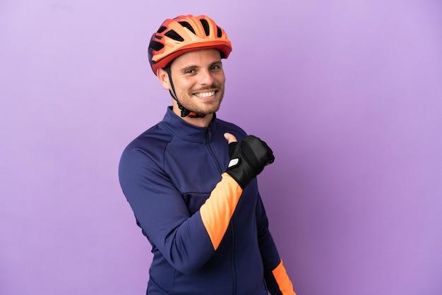 Jonge braziliaanse wielrenner man geïsoleerd op paarse achtergrond trots en zelfvoldaan