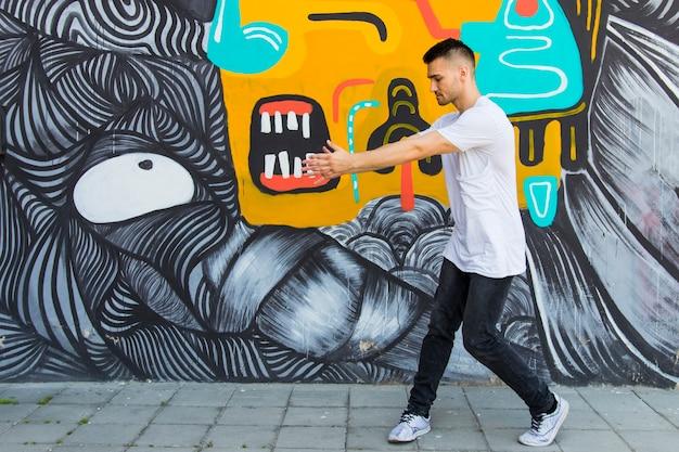 Jonge breakdancer die tegen geschilderde geweven dansen
