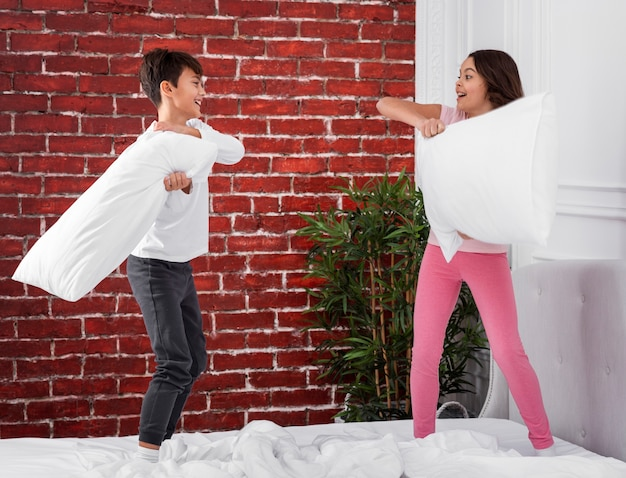 Jonge broers en zussen die thuis met hoofdkussens vechten