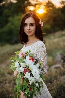 Jonge bruid buiten op een zomer weide bij de zonsondergang