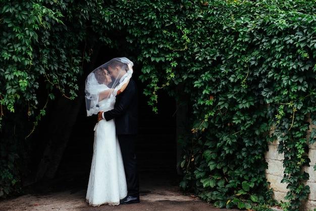 Jonge bruid die haar bruidegom in mooi park koestert
