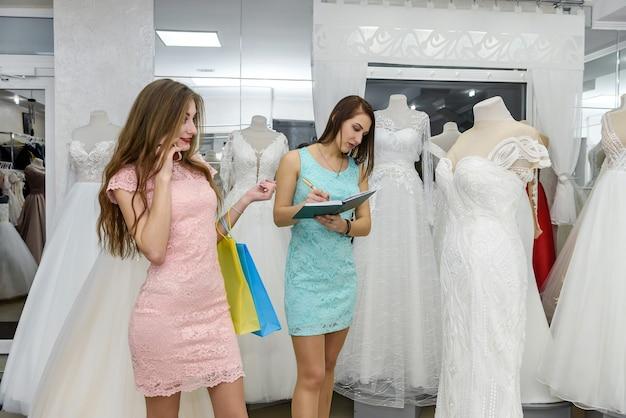 Jonge bruid die trouwjurk boekt in dealer in salon