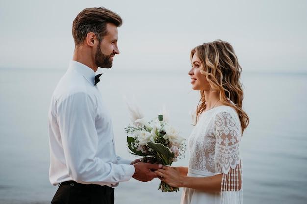 Jonge bruid en bruidegom die een strandhuwelijk hebben