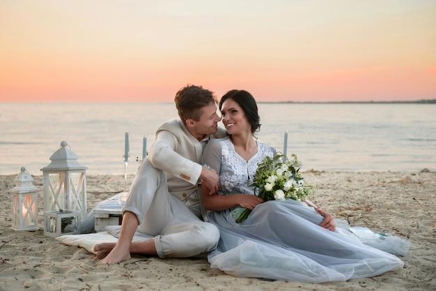 Jonge bruid en bruidegom in de buurt van de zee op het strand bij zonsondergang