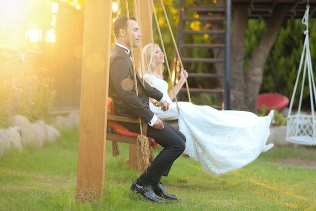 Jonge bruid en bruidegom in trouwjurk buiten trouwfoto's