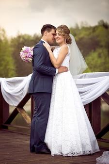 Jonge bruid en bruidegom kussen op de rivierpier op zonnige dag