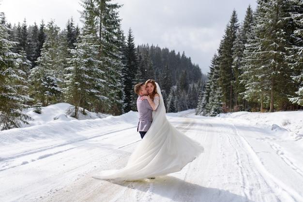 Jonge bruid en bruidegom op het besneeuwde bos