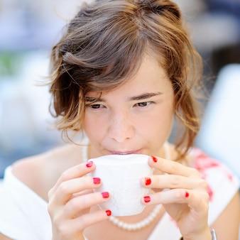 Jonge bruid het drinken koffie bij de in openlucht koffie