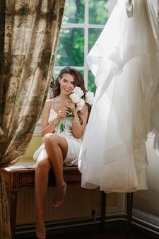 Jonge bruid houdt een bouuqet van pioenrozen plaatsing op de vensterbank in de heldere ochtend