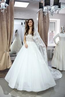 Jonge bruid in charmante trouwjurk in boutique