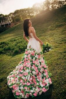 Jonge bruid in een luxe jurk loopt op het gras en kijkt terug