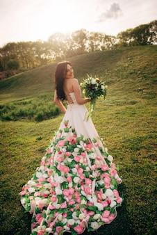 Jonge bruid in een luxe jurk loopt op het gras