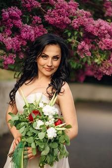 Jonge bruid in een luxe jurk van bloemen staat in een bloeiende lila tuin