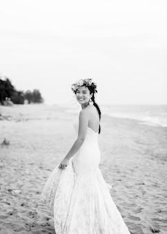 Jonge bruid in haar trouwjurk op het strand