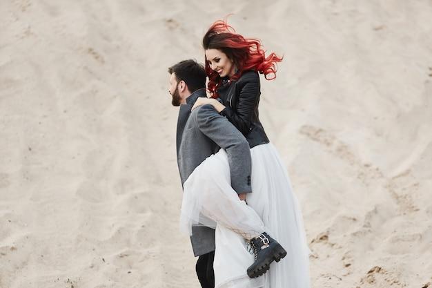 Jonge bruid in leren jas en hoed sprong op de knappe bruidegom. pasgetrouwden dollen rond in het zand. jonge vrouw in de trouwjurk gek met een stijlvolle mannen in jas. bruiloft concept