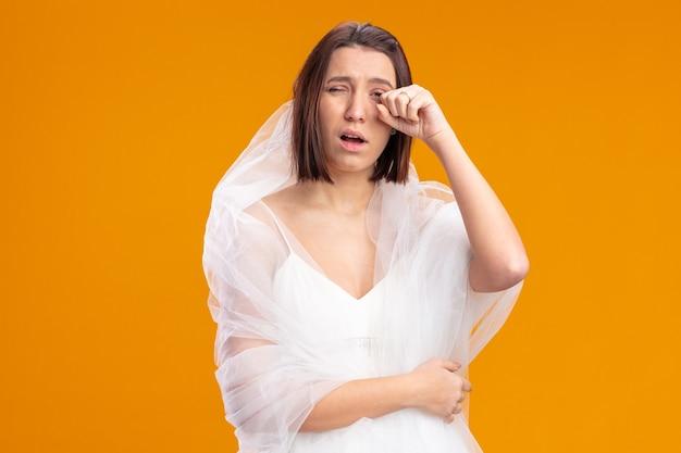 Jonge bruid in mooie trouwjurk ziet er moe en verveeld uit, wrijft over de oranje muur