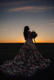Jonge bruid met een boeket in het groene veld bij zonsondergang