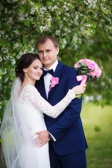 Jonge bruidegom en bruid met huwelijksboeket in bloeiende tuin