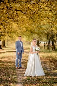 Jonge bruidegom en mooie bruid in de herfst park. focus op het meisje. het meisje blaast een bruidsboeket in haar handen.