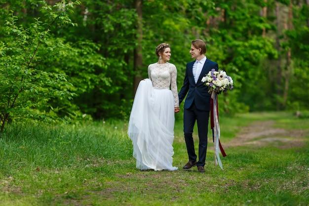 Jonge bruidspaar hand in hand en lopen samen in het park.