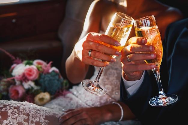 Jonge bruiloft houdt en beklimt glazen champagne
