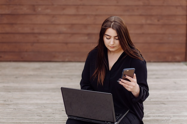 Jonge bruine haarvrouw met laptop en slimme telefooncomputerzitting op houten vloer