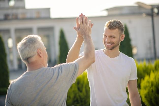 Jonge bruinharige man en grijsharige man die high five geeft