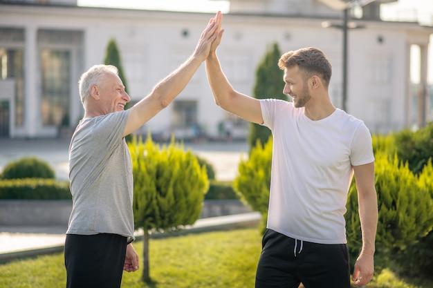 Jonge bruinharige man en volwassen grijsharige man die high five geeft