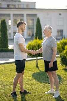Jonge bruinharige man en volwassen grijsharige man handen schudden op gras
