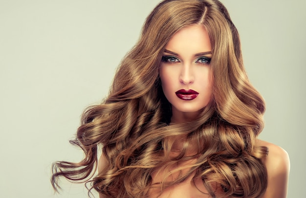 Jonge, bruinharige vrouw met elegant, omvangrijk avondkapsel. mooi model met lang, dicht, krullend haar en levendige make-up met rode lippenstift. kapperskunst, haarverzorging en schoonheidsproducten.