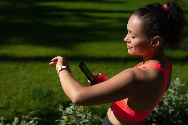 Jonge brunette atleet fitness vooruitgang controleren met behulp van fitness tracker en smartphone. training buiten